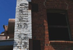 a fading ghost sign on brick building